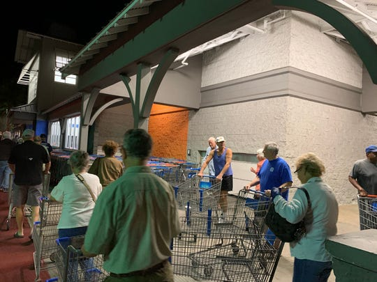 Dozens of customers at the Walmart Supercenter in Stuart line up before dawn March 24 ahead of the store's senior shopping hour.