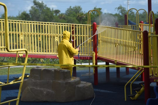 Daniel Rhoat, of the St. Lucie County Parks and Recreation department, uses a chlorine spray to decontaminate the playground at River Park Marina Tuesday, March 24, 2020, in St. Lucie County. The county is continuing to decontaminate play structures throughout the parks to help prevent the spread of the COVID-19 virus.