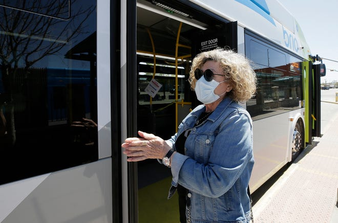 Sun Metro passenger Ursula Breckenridge uses hand sanitizer and wears a mask as she waits for her bus to leave Tuesday, March 24, 2020, in Downtown El Paso.
