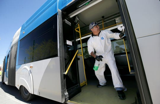 Sal Mendoza sanitizes a Sun Metro Brio bus recently at the Santa Fe Transfer Center in Downtown El Paso to help fight the spread of the coronavirus.