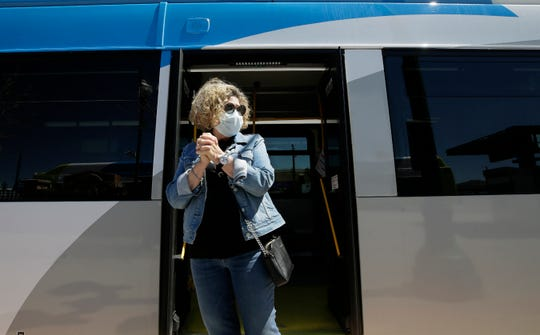 Sun Metro passenger Ursula Breckenridge uses hand sanitizer an wears a mask as she waits for her bus to depart Tuesday in downtown El Paso.