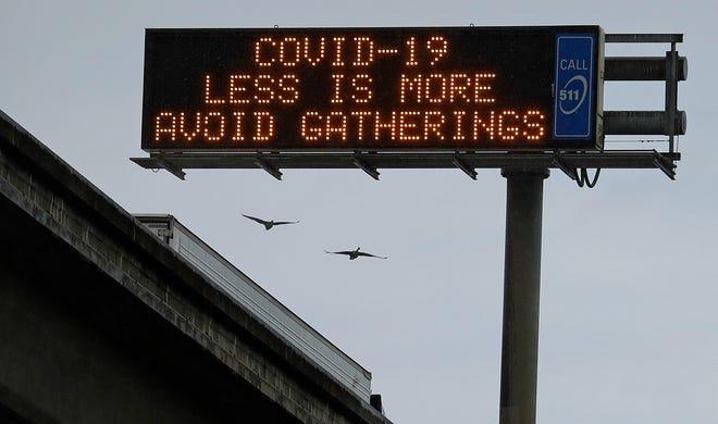 """Un mensaje en el Interestatal 880 oeste el sábado 14 de marzo del 2020 en San Leandro, California con las palabras, """"COVID-19. Menos es más. Evite las reuniones."""""""