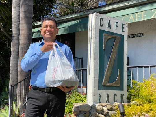 Hector Gomez, owner of Cafe Zack in Ventura, poses with a to-go lunch order. The fine-dining restaurant launched takeout service for lunch and dinner this week in response to a statewide COVID-19 order calling for the closure of sit-down restaurants.