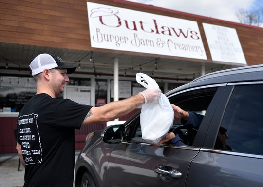 Ryan Briggs, owner of Outlaw's Burger Barn & Creamery in Vineland, brings a take-out order to a customer on Tuesday, March 24, 2020.