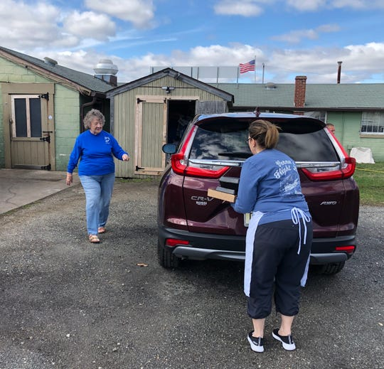 Volunteer driver Judy Lokey prepares to deliver the meals loaded into her vehicle by Verna Herman, owner of Verna's Flight Line Restaurant in Millville.
