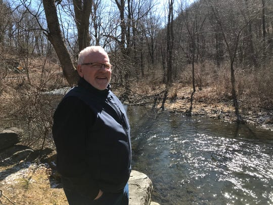 Mark Morrison, next to a stream that runs alongside his home and property in Wassiac, New York.