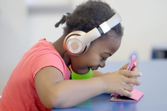 Alyssa Rogers, 7, does school work on a tablet at the Baby Cubs Learning Center in New Rochelle on March 24, 2020.
