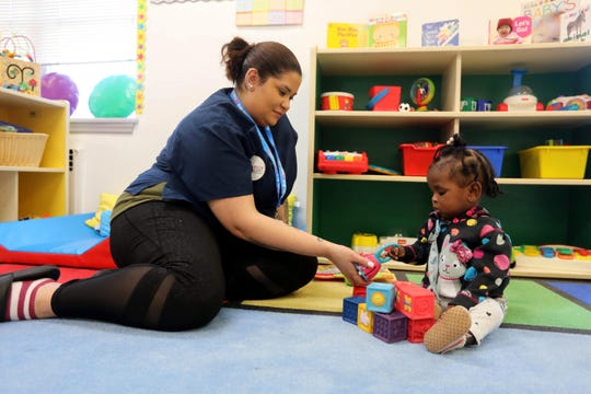 Sarah Aufiero, head teacher at the Baby Cubs Learning Center in New Rochelle, plays with Kennedy Henrquez, March 24, 2020. The daycare center has remained open during the COVID-19 pandemic to care for the children of first responders and other essential workers.