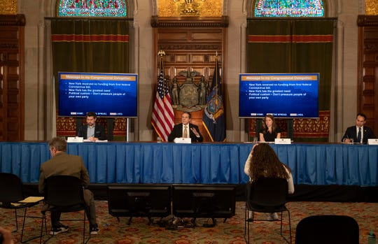 Gov. Andrew Cuomo relies on two television screens on the floor to see his PowerPoint presentations for his daily coronavirus briefings. Reporters and aides, meanwhile, are kept at a social distance.