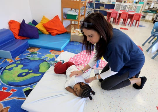 Lynn Burgess, a teacher at the Baby Cubs Learning Center in New Rochelle, rubs the back of Navee Anderson, 2, during nap time March 24, 2020. The daycare center has remained open during the COVID-19 pandemic to care for the children of first responders and other essential workers.
