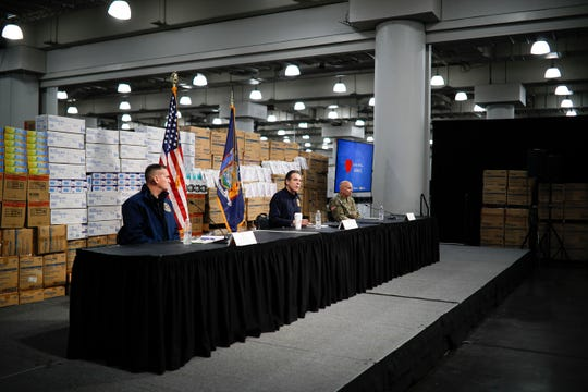 New York Gov. Andrew Cuomo, center, speaks while practicing social distancing against a backdrop of supplies during a news conference at the Jacob Javits Center that will house a temporary hospital in response to the COVID-19 outbreak, Tuesday, March 24, 2020, in New York.