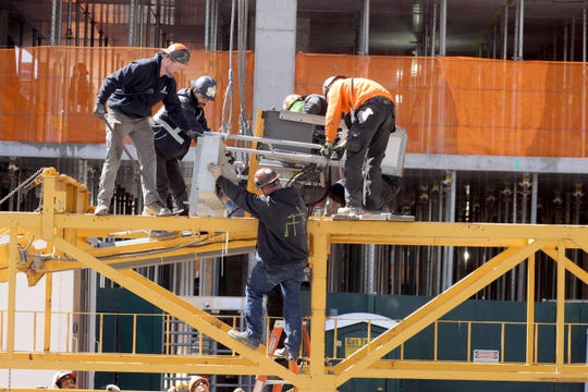 Construction workers continue work at the site of an apartment building on Lecount Place in New Rochelle, N.Y. March 24, 2020.