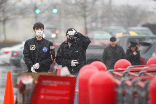 Shoppers with masks and gloves head towards the entrance of the Christiana Costco amid the coronavirus outbreak on Monday, March 23.