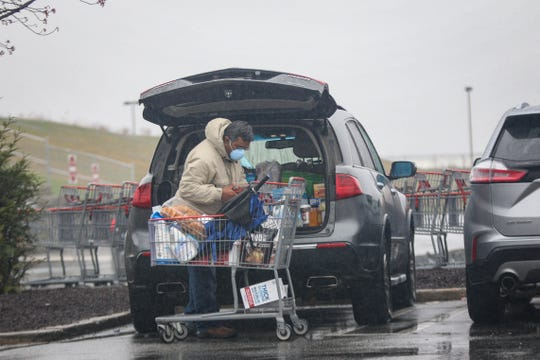 A shopper loads supplies into the car in the parking lot of the Christiana Costco amid the coronavirus outbreak on Monday, March 23.