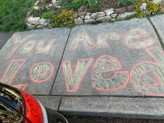 """You are loved"" was one of the messages left using chalk Jennifer Fenstermacher and Valarie Cooper distributed throughout their Wilmington neighborhood during the first week of Delaware's state of emergency."