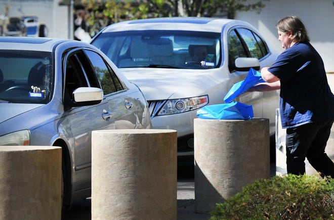 Wichita Falls Public Library, circulation supervisor, Jamie Dollar delivers books to a pre-determined concrete pillar located outside of the library as part of the no contact curbside delivery, Tuesday morning. People wanting to pick up books are asked to stay in their cars, show their library card and retrieve the books from the pillar.