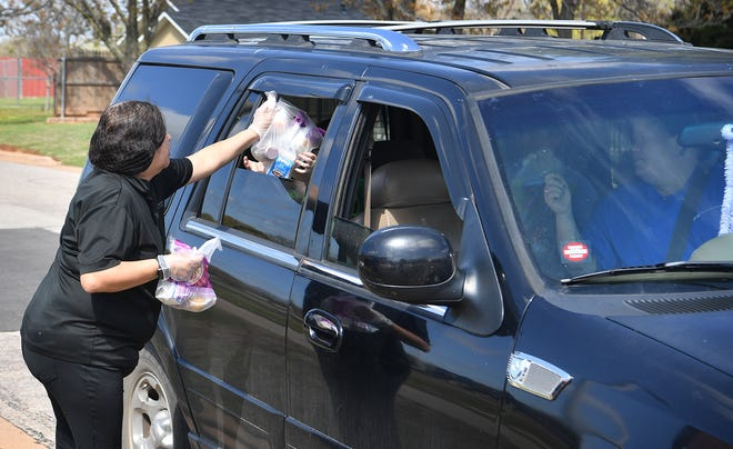 Scotland Park Elementary cafeteria worker Helen Ponce hands out Nacho Fun Lunches Tuesday in the Grab and Go lunch distribution program.