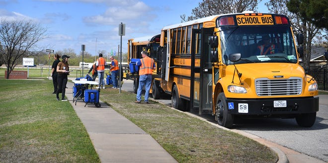 Emily Kincaid, marketing specialist for Chartwells K12, coordinates distribution of school lunch March 24, 2020, at Scotland Park Elementary. These lunches are available to all WFISD students under 18 even though schools are closed. There is no need to be qualified for free or reduced lunches for a student to receive them.
