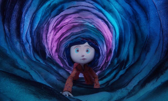 "A curious girl (voiced by Dakota Fanning) travels through a portal between worlds in ""Coraline."""