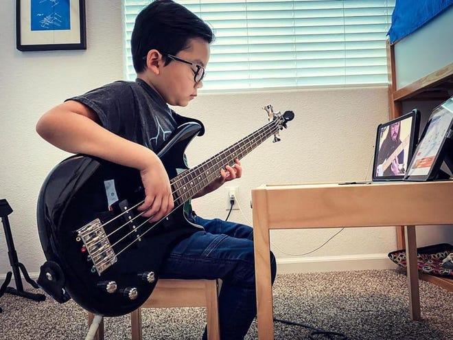 A student participates in a remote lesson through School of Rock.