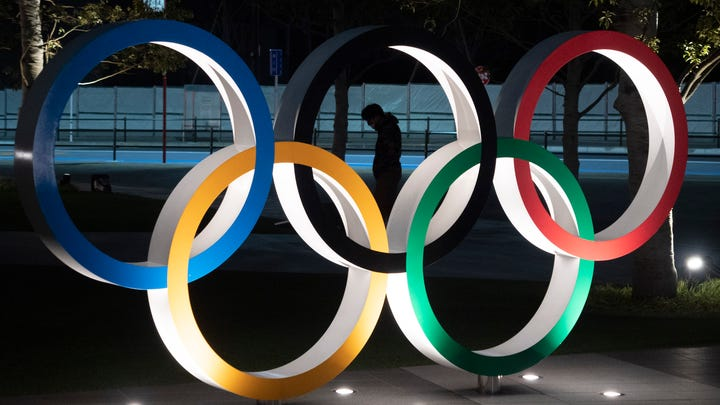 A man is seen through the Olympic rings in front of the New National Stadium in Tokyo, on March 24, 2020.