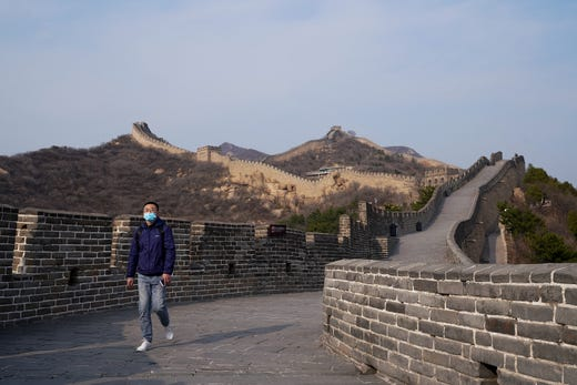 A Chinese tourist wears a protective mask as she visit the almost empty Badaling Great Wall on March 24, 2020 in Beijing, China. Affected by the new coronavirus covid-19, the Badaling Great Wall closed on Jan. 25.