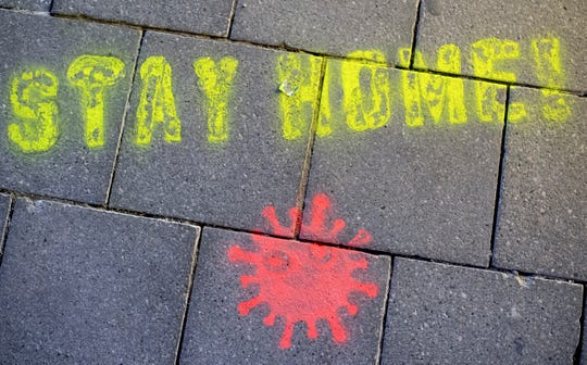 "A graffiti consisting of the text ""Stay Home"" and a symbolic novel coronavirus has been sprayed on the ground in Munich, Germany, Monday March, 16, 2020."