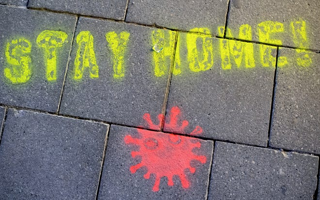 """A graffiti consisting of the text """"Stay Home"""" and a symbolic novel coronavirus has been sprayed on the ground in Munich, Germany, Monday March, 16, 2020."""