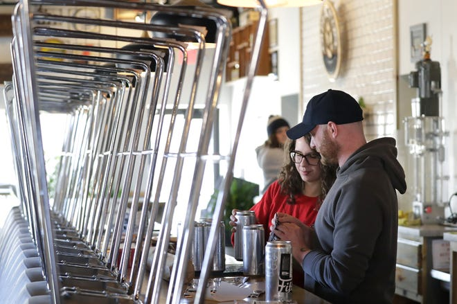 Bartenders Anna Van Pay, left, and Andrew Beulen fill a take out beer order on March 21 at the Fifth Ward Brewing Company in Oshkosh. The brewery has since closed its taproom and now offers curbside pickup only.