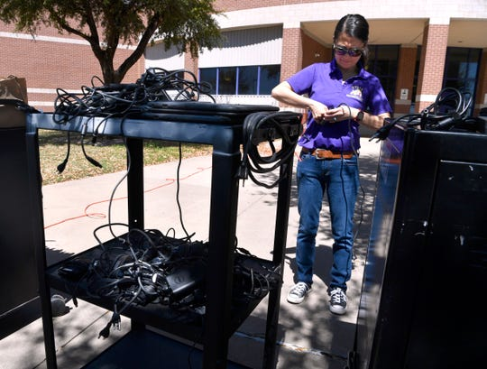 Wylie ISD technology specialist Sarah Cornelius prepares laptops for parents to pickup Wednesday in front of Wylie High School.