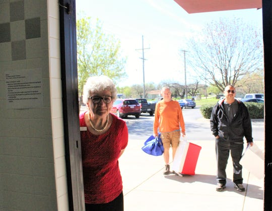 Meals on Wheels director Betty Bradley peeks from the bright sun outside into the indoor staging area to see if two more volunteers can enter Wednesday. First-time volunteers are helping to keep the delivery program going; Bradley is making sure no more than 10 are inside collecting wrapped meals and beverages enclosed in bags, which is standard operating procedure. A note on the wall, left, provides tips on how to deliver meals safely.