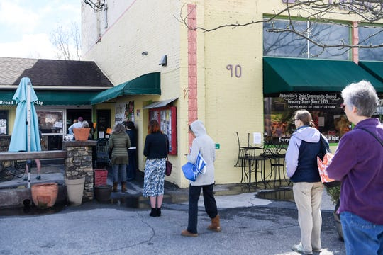 People wait in line to shop at the French Broad Co-Op downtown Asheville March 25, 2020. Many stores have placed limits on the amount of people allowed inside at one time to help people maintain social distance during the coronavirus pandemic.