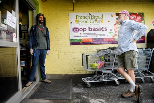 Jordan Davis, left, talks to Weogo Reed at the door of the French Broad Co-Op March 25, 2020 in downtown Asheville while they wait for shoppers inside to exit. Many stores have placed limits on the amount of people allowed inside at one time to help people maintain social distance. Davis helped customers to prevent the spread of coronavirus while shopping by handing out gloves and sanitizing cart and door handles.