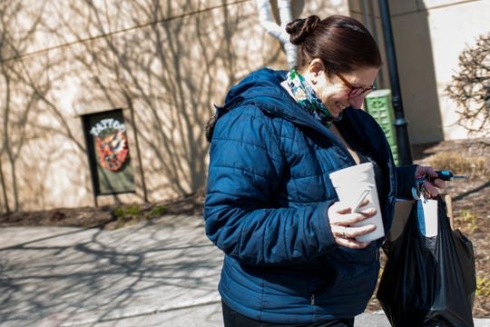 """Connie Jones carries a lunch order from Griffin Grill & Pub on Wednesday, March 25, 2020 in Battle Creek, Mich. Griffin Grill & Pub is filling takeout and delivery orders while Michigan is under a """"stay home"""" order to slow the spread of COVID-19."""