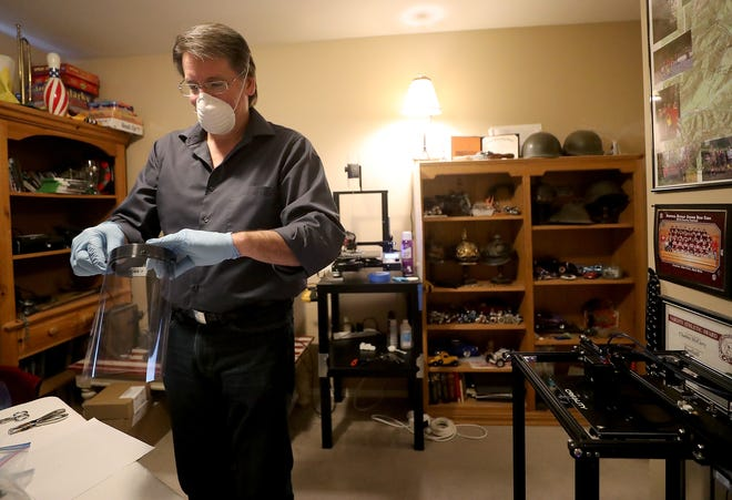 Steven Ward puts together a face shield using a frame that he created on one of the 3D printers at his Poulsbo home on Wednesday. Ward bought a 3-D printer to make Dungeons and Dragons characters. Now, he's working with the Navy and manufacturing hundreds of shields for emergency responders and health care providers.