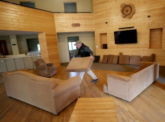 Wade Zick, managing director of Pilgrim Firs Camp & Conference Center, places freshly washed couch cushions back into place on Wednesday as he readies the South Lodge for first responders and medical personnel who may need a place to isolate because of COVID-19.