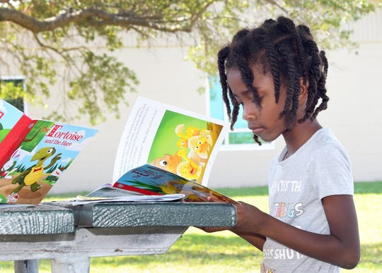 Club Esteem member Jalyna Maestre, 16, tutoring A'nyla Dennard, 7, at right. Adults and teens of Club Esteem, Inc. are set up outside the Lipscomb Park Community Center on Monroe Street in South Melbourne, providing free breakfast and lunch meals for pick up with the help of Second Harvest Food Bank of Brevard and The Children's Hunger Project. They are set up 10am-1pm Mon-Fri , and hope to continue the meals in the coming weeks. Their mission is to inspire young people from economically disadvantaged communities to pursue academic and personal excellence. This non-profit is always in need of donations. Visit www.clubesteem.org.
