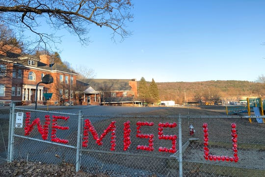 """Red plastic cups spell out """"We miss you"""" in the fence of the White River School in Hartford on Sunday, March 22, 2020. The school, like the rest of the state, is temporarily shuttered due to concerns about the coronavirus pandemic."""