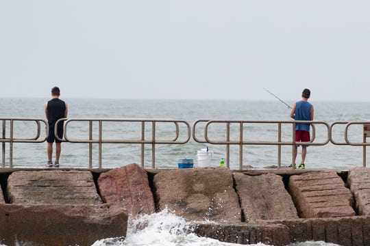 People fish along the jetties along the Packery Channel on Wednesday, March 25, 2020.