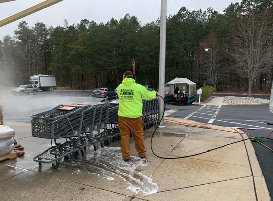 James Dalton, co-owner of Revive Painting & Powerwashing, a Medford -based company, sanitizes the shopping carts at Murphy's Fresh Market in Medford. He and his business partner Tom Davis are donating their services to several grocery stores in their town during the coronavirus crisis.