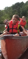 John Marandola makes a funny face while canoeing with his sisters, Hope and Zoey. John was battling brain cancer but his prognosis has improved significantly.