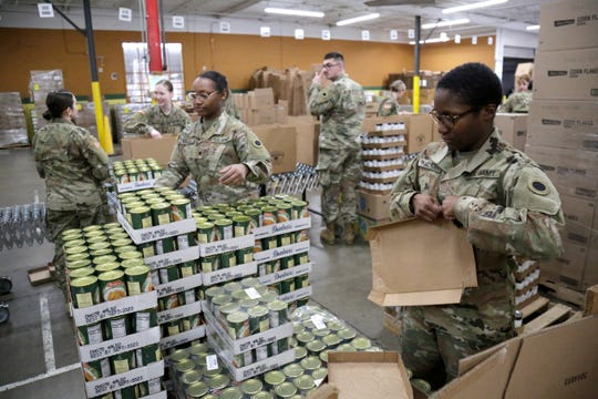 Soldiers pack supply boxes to be distributed at the Freestore Foodbank Mayerson Distribution Center in the Paddock Hills neighborhood of Cincinnati on Monday, March 23, 2020. The Ohio National Guard was deployed to the Distribution center on an ongoing mission to pack and distribute food and supplies to those in need.