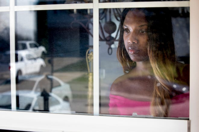 Monique Conyers looks outside her front window on Wednesday, March 25, 2020, in Union, Ky. Conyers said she is unable to make house calls or see her clients through her company that serves children who are at risk of abuse or who have suffered abuse.