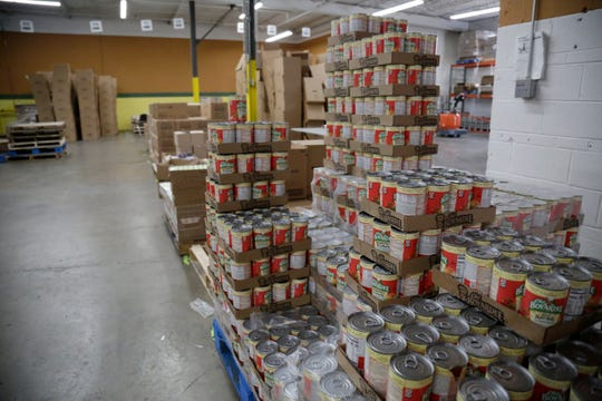 Cans of ready to eat pasta are stacked before being distributed into supply packages at the Freestore Foodbank Mayerson Distribution Center in the Paddock Hills neighborhood of Cincinnati on Monday, March 23, 2020. The Ohio National Guard was deployed to the Distribution center on an ongoing mission to pack and distribute food and supplies to those in need.