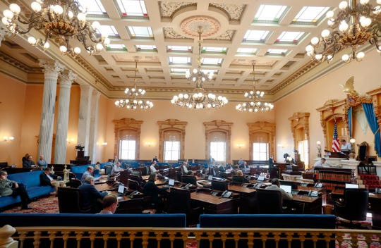 The Ohio Senate was in session at the Ohio Statehouse on Wednesday, March 25, 2020. Sentators took precautions against coronavirus including spacing themselves through the Senate chambers and using hand sanitizer. Some staff members wore gloves.