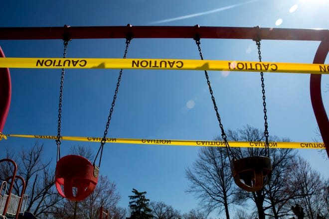A view of swings wrapped in caution tape at Carson Covedale Park in West Price Hill on Wednesday, March 25, 2020. The playground has been shut down due to the new coronavirus pandemic.