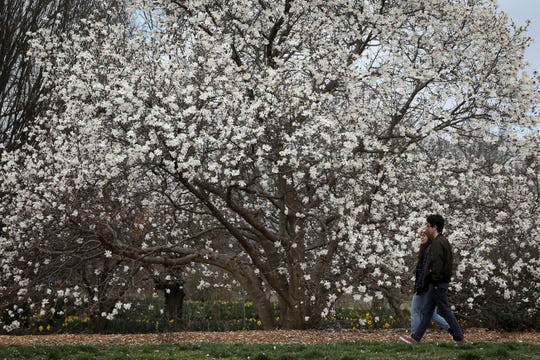A man and woman walk through Ault Park, Monday, March 23, 2020, in Cincinnati.