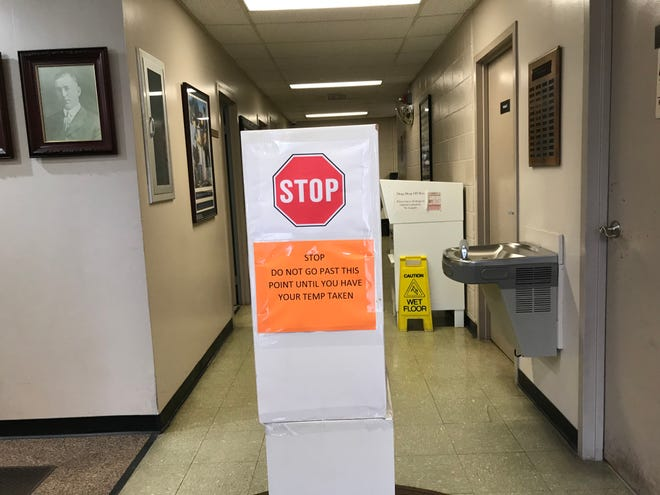A sign on a post in the Coshocton County Sheriff's Office requesting those entering to stop and have their temperature taken before going farther.