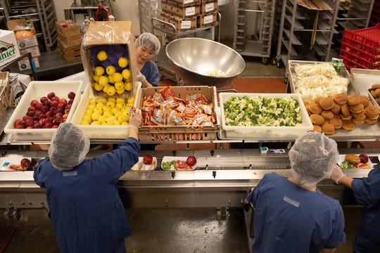 Des Moines Public Schools employees prepare meals for the district's grab-and-go food distribution sites.