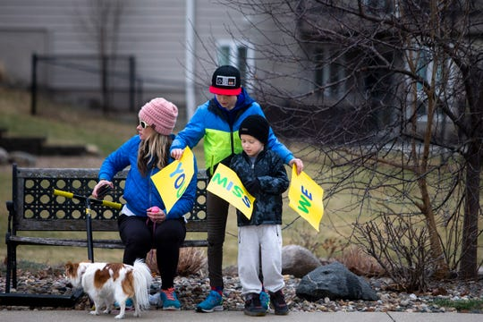 Sam Van Hemert, 6, and Gabe Van Hemert, 11, work out how to hold their signs as they wait for the Johnston elementary school's teacher parade to drive by on Wednesday, March 25, 2020, in Johnston. Teachers from Johnston's elementary schools drove through the neighborhoods waving and honking their car horns.